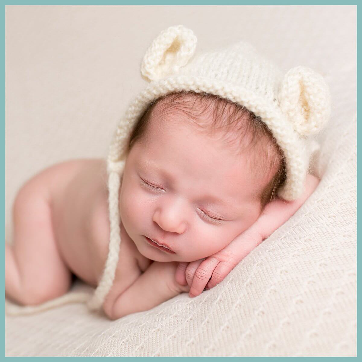 Newborn baby posed with hands under chin, wearing a cream teddy bear hat