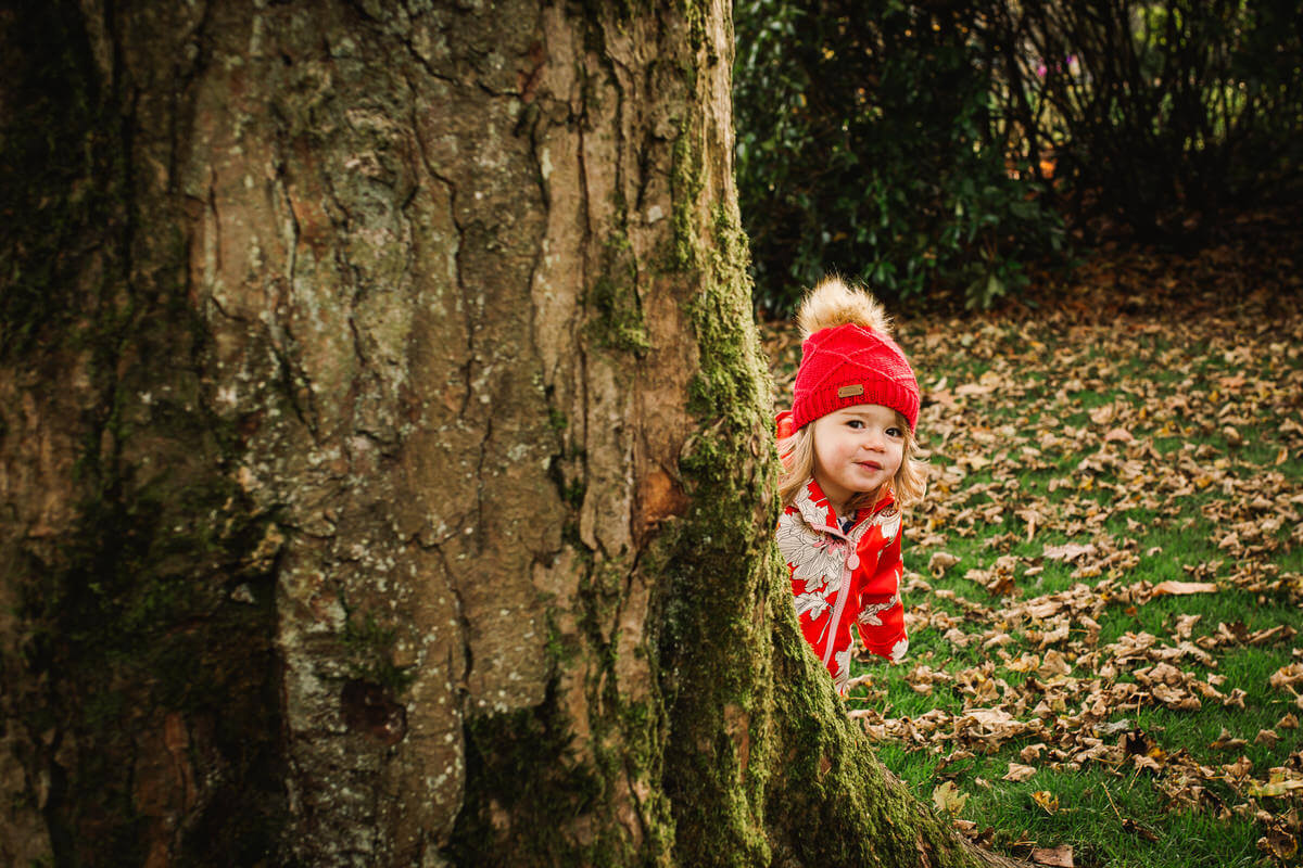 Outdoor photo shoot, little girl wearing red hat and jacket