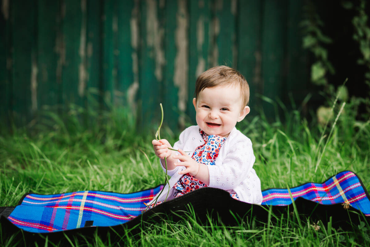Baby sat on picnic blanket playing with flowers