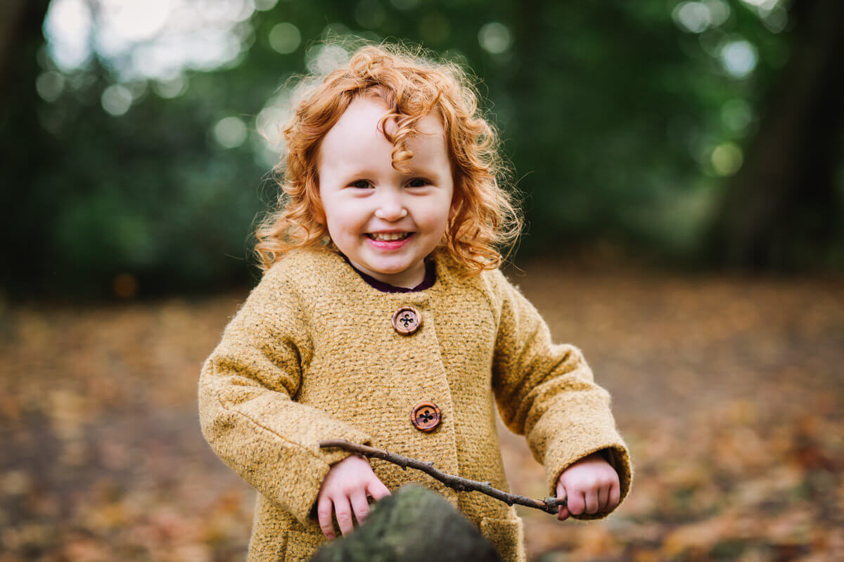Little girl with red hair at autumn time
